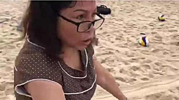 Người phụ nữ giải thích chặt lưới bóng chuyền của khách tây